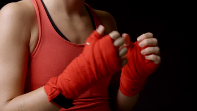 Female boxer checking her wrapped fists, close-up shot video