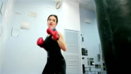 female boxer, self-defense training in the gym, Girl in boxing gloves for sports, kicking on the punching bag, power sport for women, a dangerous woman video