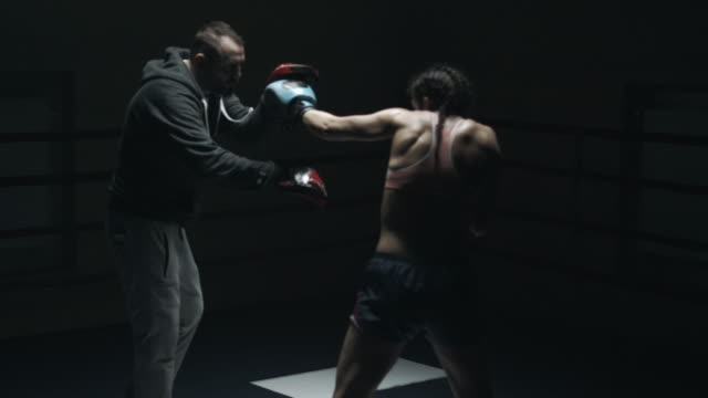 Female boxer sparring with her trainer video