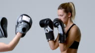 Female boxer training against mitts of a sparring partner, shot on R3D video