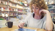 Female browsing a digital tablet in a library. video
