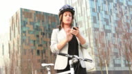 Female Business executive on phone holding Bicycle outside office video