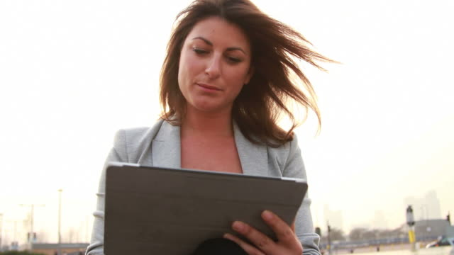 Female Business executive working on ditigal tablet outside video