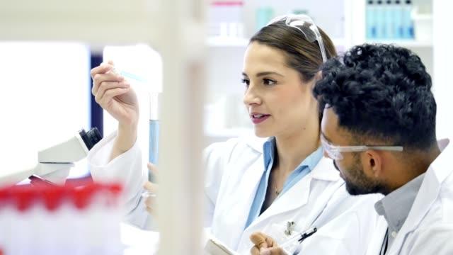 Female chemist analyzes liquid in a test tube video
