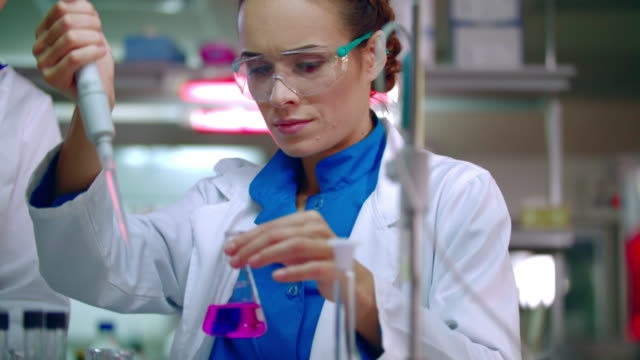 Female chemist doing chemical experiment. Chemical reaction in glass flask video