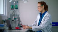 Female chemist in lab. Chemistry research. Woman chemist doing chemical research video