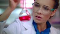Female chemist in lab. Woman chemist analyzing chemical liquid in lab flask video