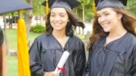 Female college or high school graduates congratulate one another after graduation video