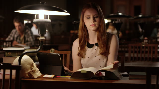 DS Female college student using her tablet and books in the library video