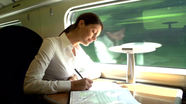Female Commuter On Train Working On Document video