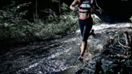 SLO MO DS Female competitor running on a muddy trail at night video