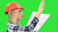 Female construction engineer reading plans and talk to workers on a Green Screen, Chroma Key video