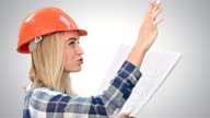 Female construction engineer reading plans and talk to workers on white background video