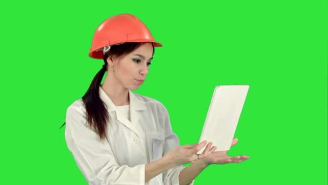 Female construction specialist in hardhat having a video call via tablet on a Green Screen, Chroma Key video