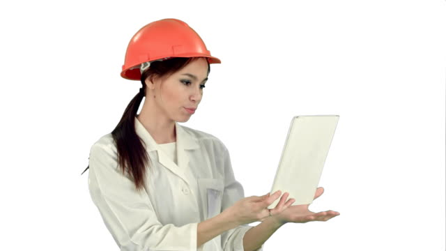Female construction specialist in hardhat having a video call via tablet on white background video