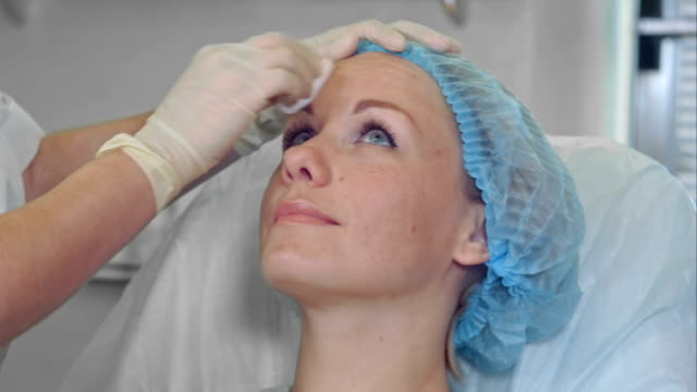 Female cosmetologist cleansing with sponge face of a female client of beauty salon video