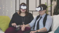 Female couple eating popcorn with VR headsets in their living room watching a virtual reality film video