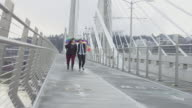 Female couple skipping across a pedestrian bridge draped in a gay pride flag and smiling video