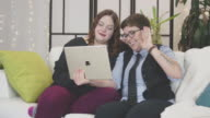 Female couple talking on a digital tablet to a loved one and waving at the screen from the comfort of their home video