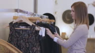 Female customer is sorting through clothes at small business boutique video