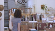Female customer is sorting through jewelry at small business boutique video