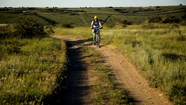 Female cyclist riding on a mountain road on a mountain bike video