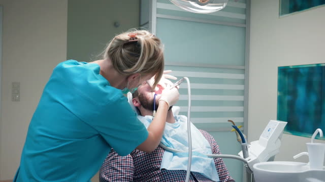 Female dentist drilling patient's tooth in dental clinic. Steadicam. video