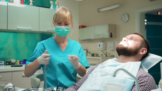 Female dentist drilling tooth of male patient. Slider shot, right. video