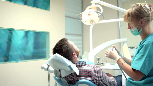 Female dentist drilling tooth of patient in dental clinic. Slider shot, right. video