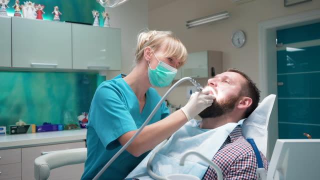 Female dentist drills patient's tooth. Patient rinses teeth. Steadicam. video