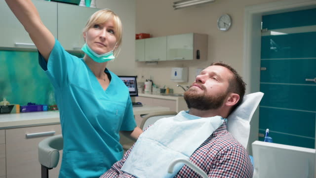 Female dentist examining teeth of male patient and looking to camera. video