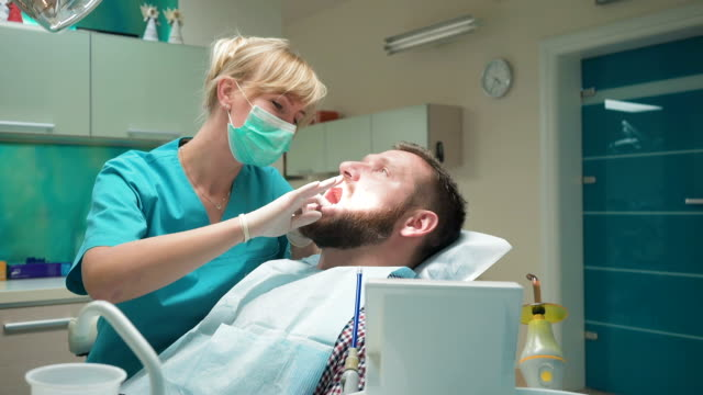Female dentist examining teeth of male patient, looks to the camera. Slider shot video