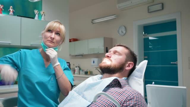 Female dentist examining teeth of male patient. Steadicam. video