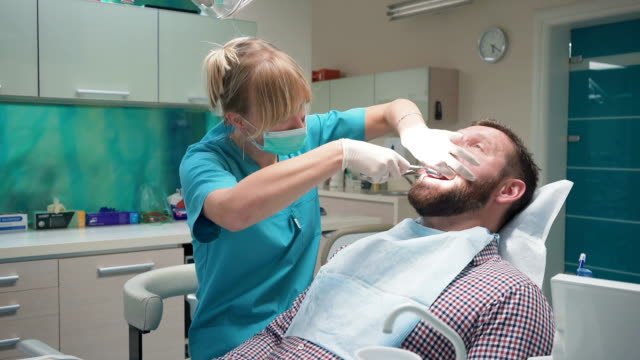 Female dentist extracting patient's tooth. Steadicam. video