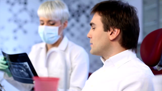 Female dentist showing male patient x-rays video
