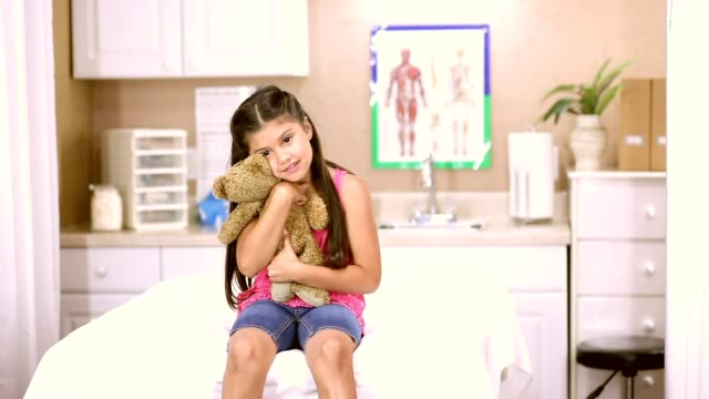 Female doctor and latin descent girl patient in pediatrician's office or clinic. video