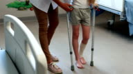 Female doctor assisting girl to walk with crutches video