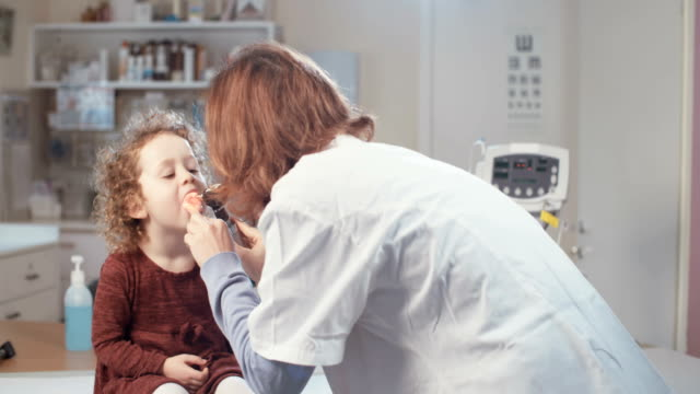 Female doctor chaecking a little girl in the clinic video
