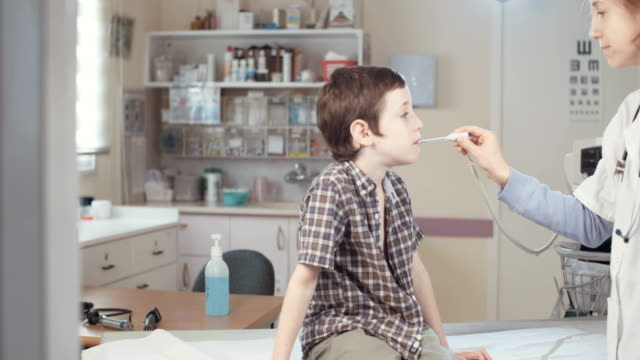 Female doctor chaecking a young boy in the clinic video