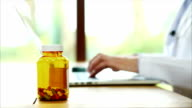 Female doctor checking prescription label information on laptop video