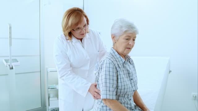 Female doctor checking the senior womans back video