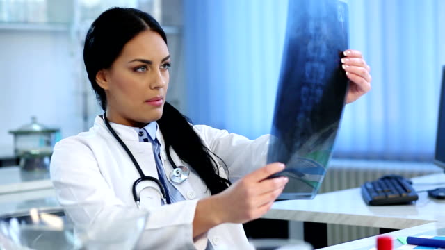 Female doctor examining spine X-ray video