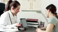 Female doctor explaining something on tablet computer video