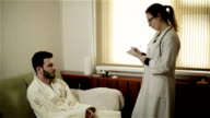 A female doctor giving a prescription to a male patient. video
