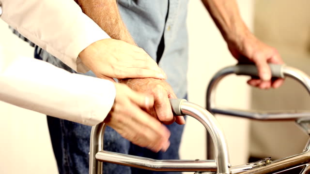 Female doctor helps senior man patient use walker. Holding hands. video