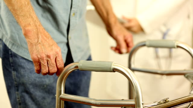 Female doctor helps senior man patient use walker. Holding hands. video