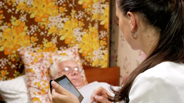 A female doctor interrogates a patient at home. She writes an anamnesis to the tablet computer video