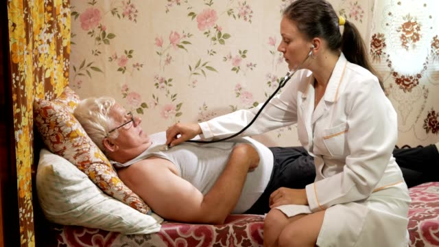 A female doctor listens to a patient with a phonendoscope at home. The man is lying on the couch video