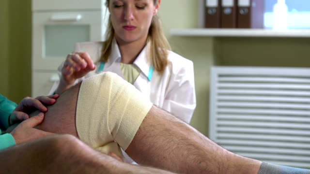 Female doctor puts a tight bandage on the injured knee of the patient. Close-up video