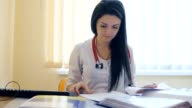 Female doctor reading and writing notes in records in hospital video